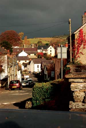 The old houses of the town of Clun go down the hill towards the bridge and the river with a dark winter sky above.