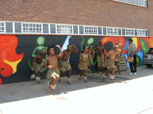 A group of black dancers are performing energetically in front of brightly coloured painted murals. On the right, a black man, wearing an elaborate beaded collar, is accompanying them on a drum.