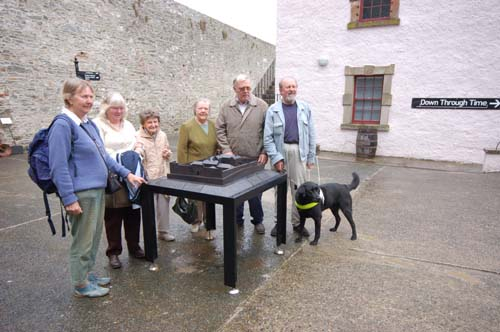 Four women and two men stand around the tactile bronze model of Down County Museum. The man at the right of the picture has a Guide Dog with him.