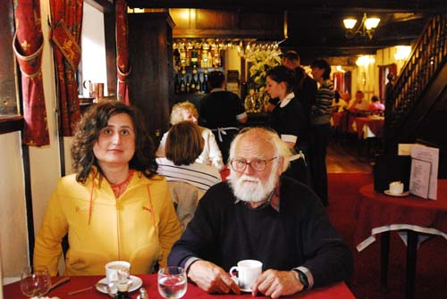 Peter and Maggie are sitting at a table having tea at the famous De Greys cafe. Maggie has shoulder length brown hair and is wearing a yellow jacket. Peter has white hair and a white beard and is wearing a blue jersey. Behind them are the waitresses in their black dresses and white aprons.